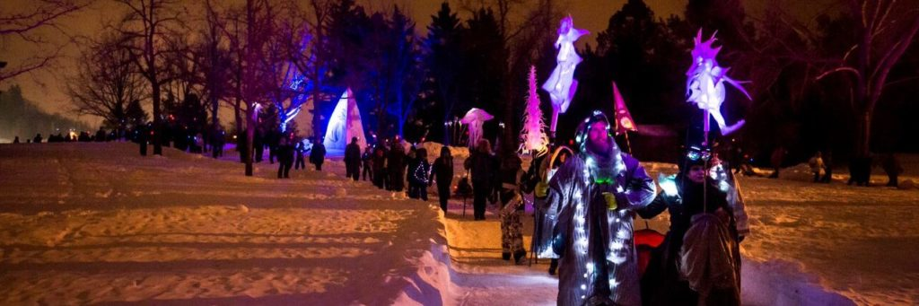 A procession of artists walk through snowy Hawrelak Park during a winter night, holding lanterns and lamps.