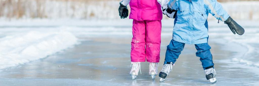 Two kids, one in pink and one in blue, skate along an IceWay