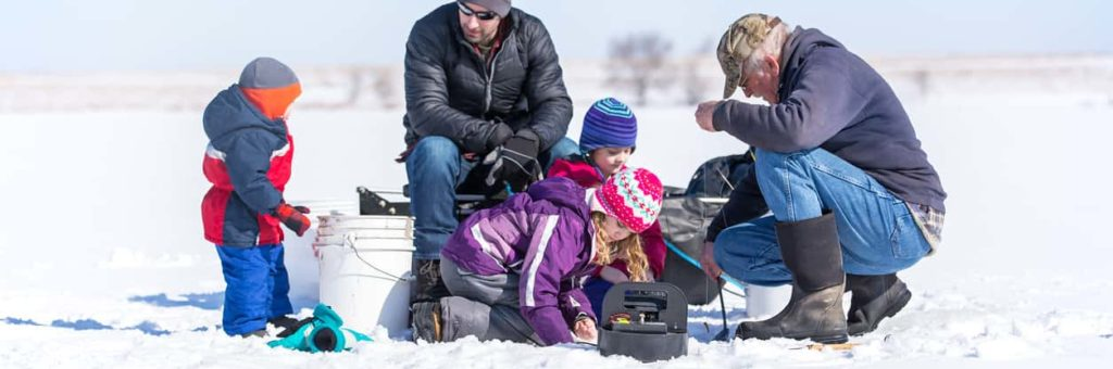 A family huddles around an ice fishing hole on a sunny winter day