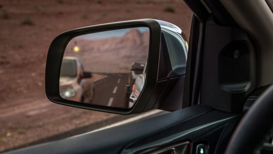 A rear-view side mirror on a Ford Ranger, alerting the driver theres a vehicle in the blind spot with the BLIS indicator light
