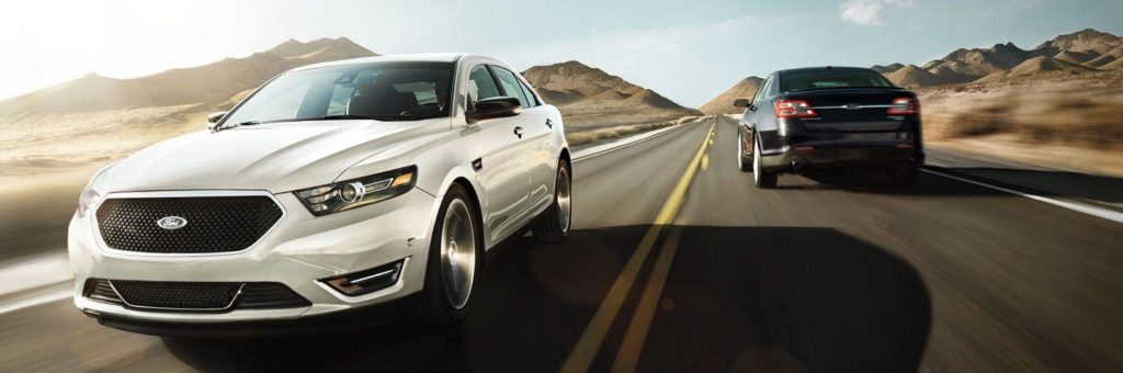 A white Ford Taurus passes another vehicle on a highway drive