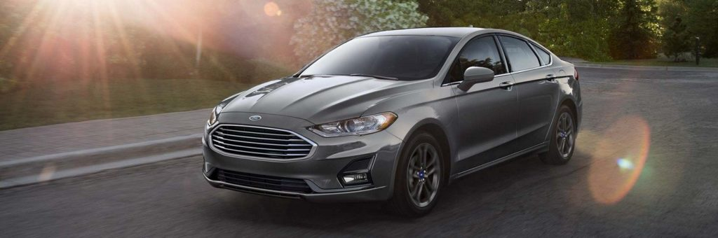 A grey Ford Fusion drives down a country road