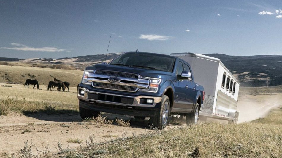 A blue Ford F-150 King Ranch hauls a trailer down a dusty trail on a sunny prairie day