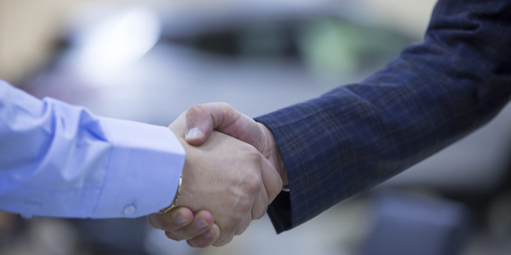 Two men shake hands in front of a silver SUV in a vehicle showroom