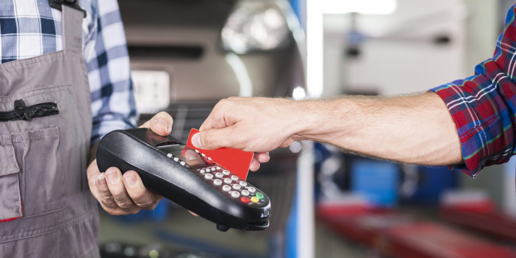Customer paying with credit card machine payment at car service