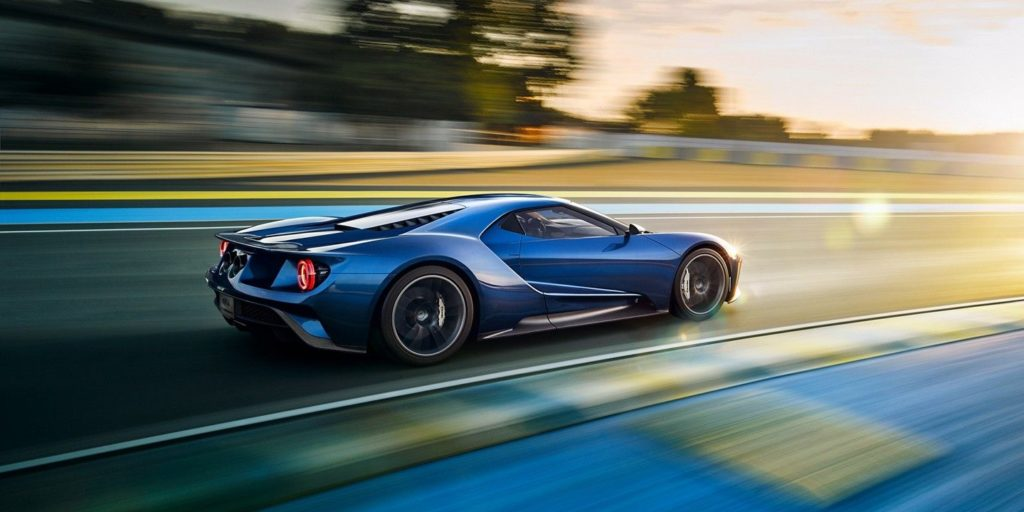 A blue Ford GT races down a blurry road at high speed