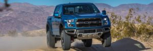 A blue Ford F-150 Raptor gets some air over rough, off-road desert terrain