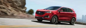 A red Ford Edge ST going around a mountain bend on a sunny day