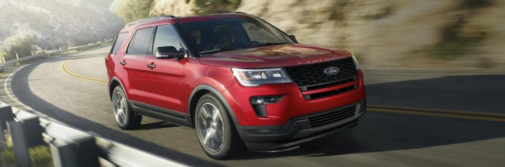A red 2019 Ford Explorer races around a mountain bend