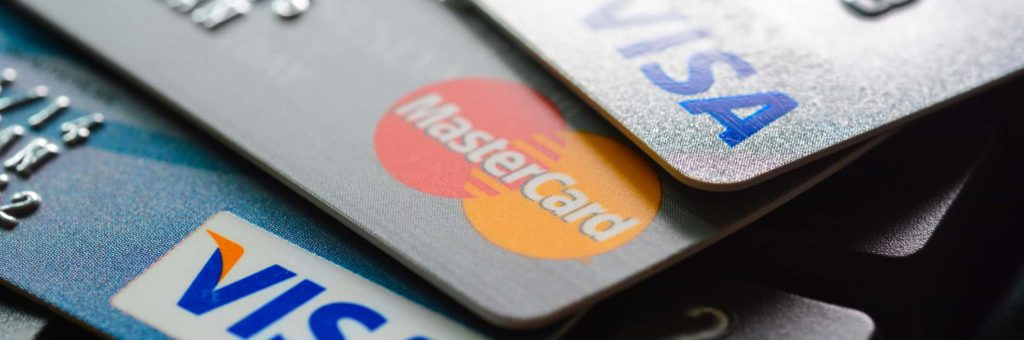 A stack of credit cards, Mastercard and Visa logos prominently displayed