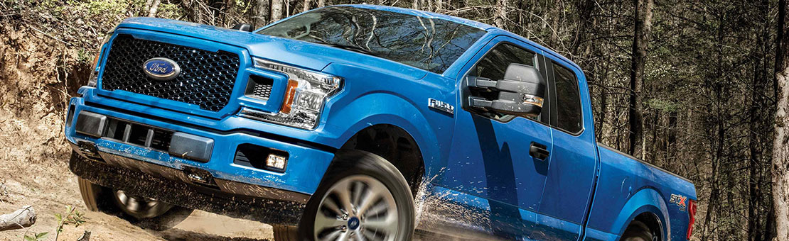 A blue Ford F-150 drives through a wooded terrain, kicking up a cloud of dust