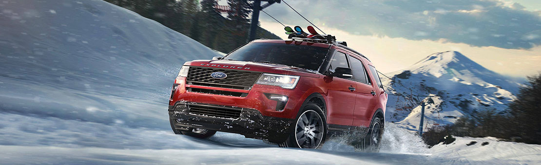 A red Ford Explorer drives through the snow, up a ski hill