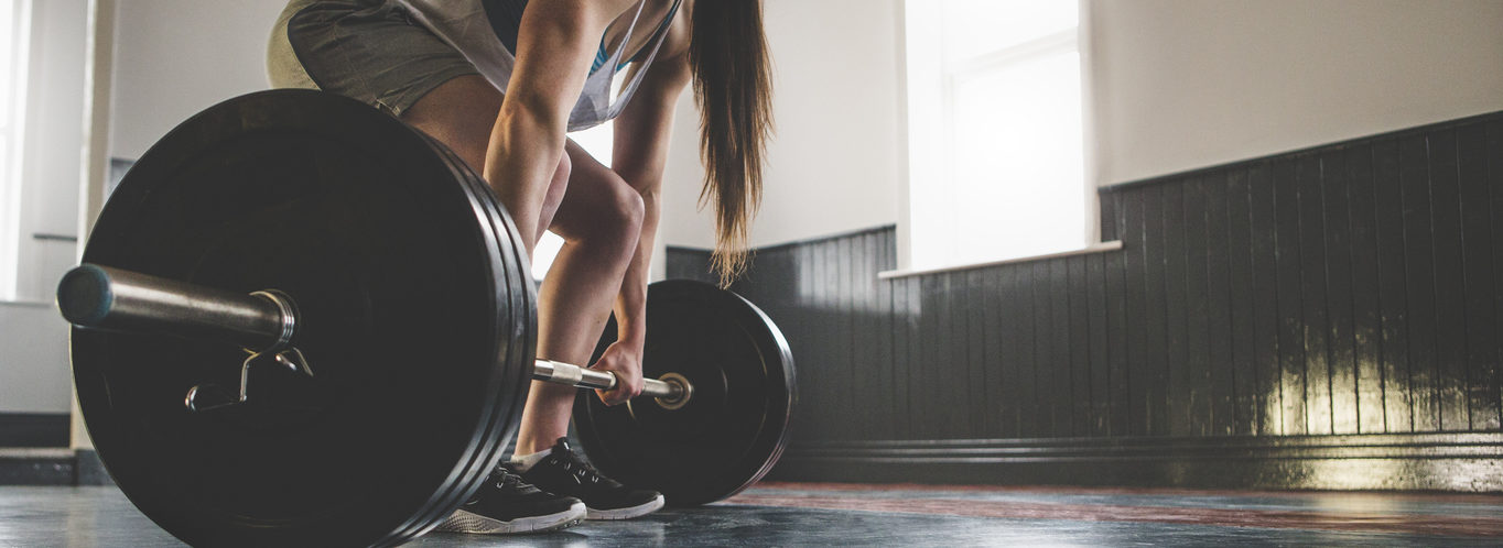 Muscular professional female powerlifter doing a deadlift in an empty gym space, copy space is on the right side of the image.