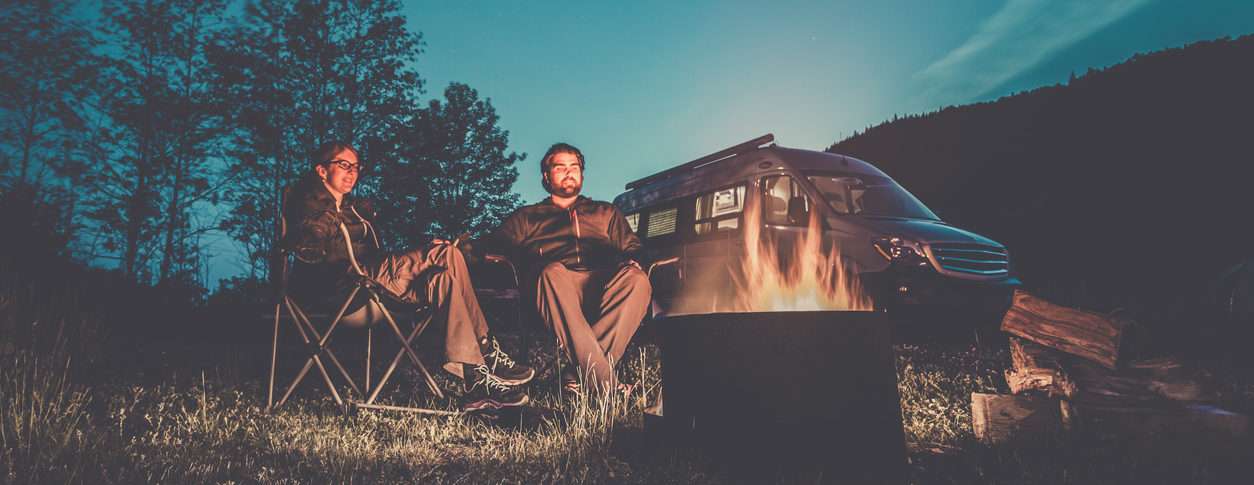 Heterosexual Couple Sitting Next to the Campfire with a Camper Van in the background. They are holding their hands.