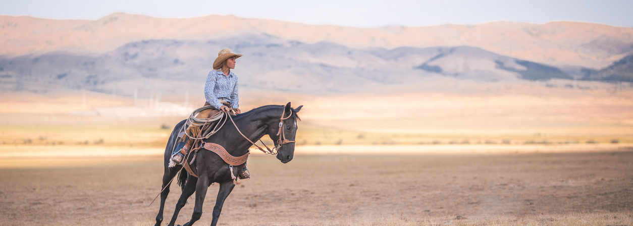 Cowgirl is riding a horse. Beautiful nature in the back in Utah, USA.
