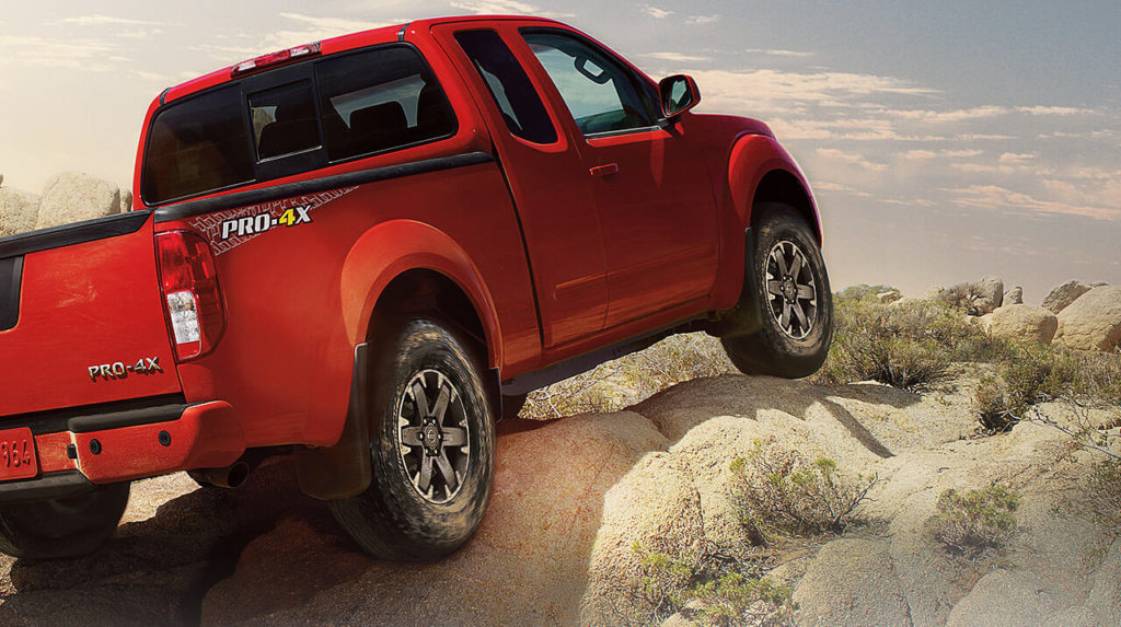 the 2019 nissan frontier in red, driving over some rocks