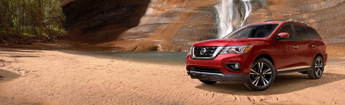 3/4 view of a 2019 Nissan Pathfinder parked by a waterfall