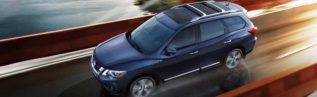 3/4 bird's eye view of 2019 Nissan Pathfinder driving on wet road