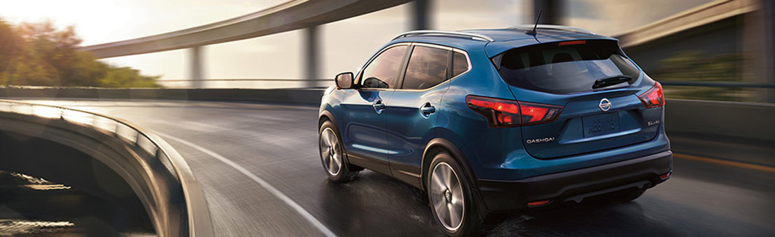2019 Nissan Qashqai driving on wet road shown in Caspian Blue