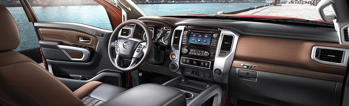 2019 Nissan Titan XD interior shown in Black/Brown Leather, highlighting centre console