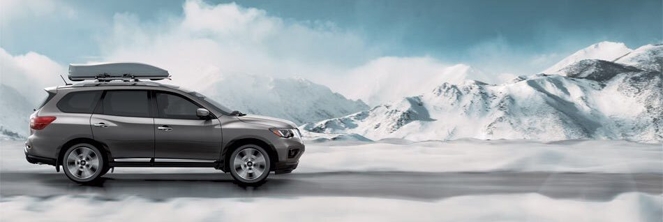 Nissan Pathfinder driving on snowy mountain-adjacent road