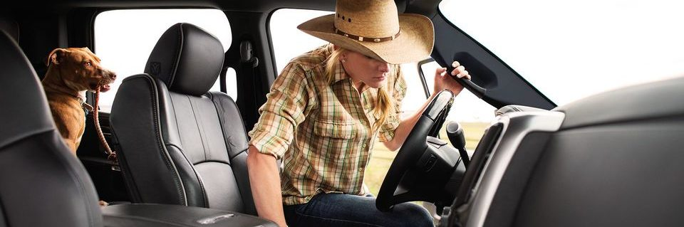 Interior shot of blonde woman with cowgirl hat getting into the drivers seat with brown dog in back,, the dog has rope in its mouth.