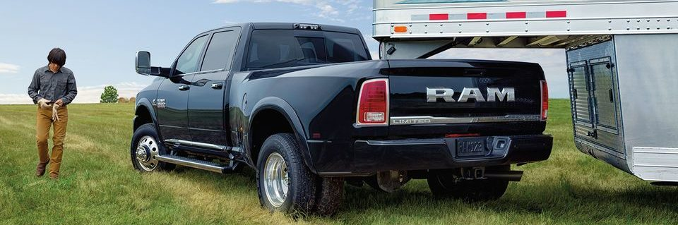 Ram 3500 limited edition tail end shot backing into trailer, farm worker beside driver side door putting on tan work gloves