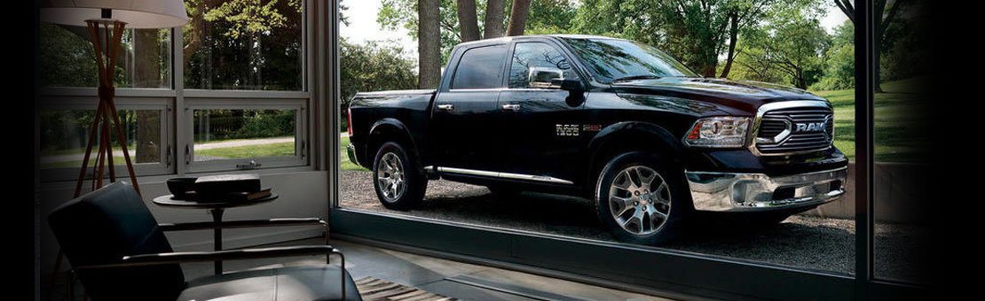 Black Ram 1500 parked outside large residential window, window overlooks greenery