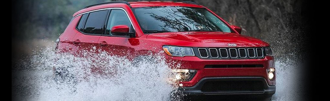 Red Jeep Compass driving through deep water