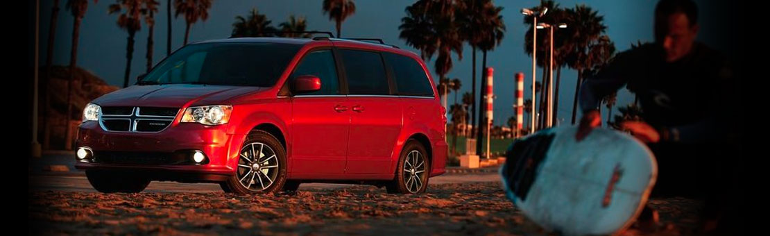 Red Dodge Grand Caravan parked on beach at sundown, surfer waxes board