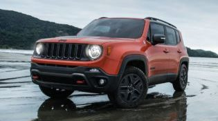 An orange 2018 Jeep Renegade drives effortlessly across a wet, sandy beach