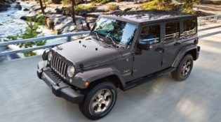 A gray 2018 Jeep Wrangler JK crosses a bridge somewhere in the hilly backcountry
