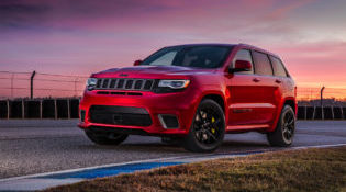 A red 2019 Jeep Grand Cherokee masters a rural road