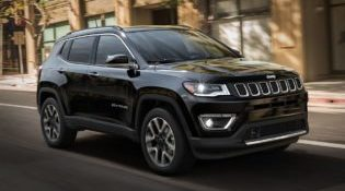A 2019 Jeep Compass cruises down a sunny city street