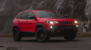 A red 2019 Jeep Cherokee sits on a mountain road, ready for adventure
