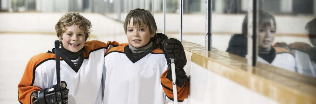 Two players in a youth hockey program smile for the camera