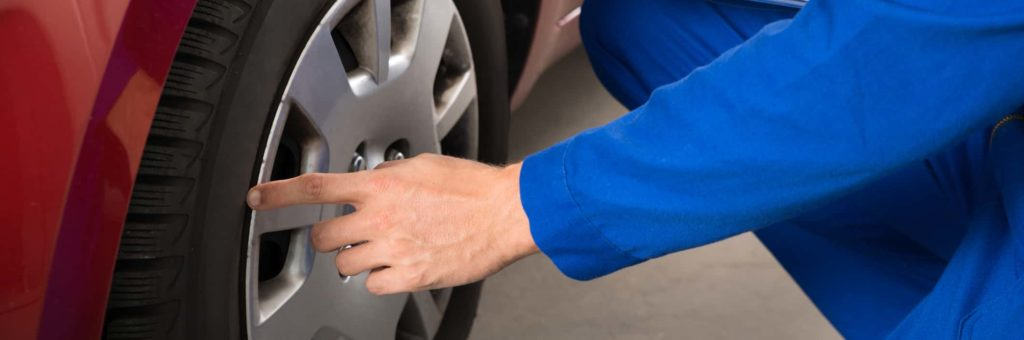 A service technician looks at a professionally replaced tire