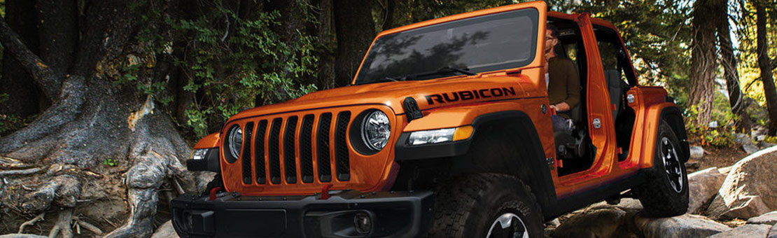 An orange Jeep Wrangler Rubicon drives over rocky forest terrain