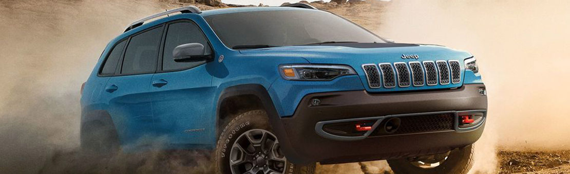 A blue Jeep Cherokee driving on sand, kicking up a cloud of dust behind it