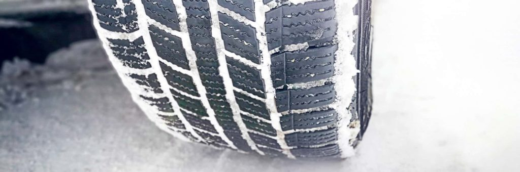 A closeup on a winter tire driving on a snowy road
