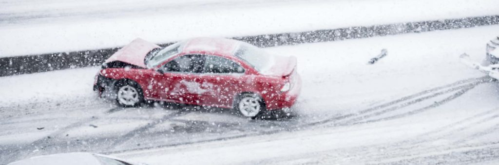 A red car on the side of a snowy road, facing the wrong way, the front crumpled from a collision