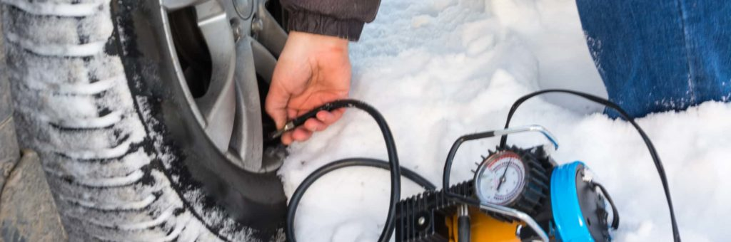 A man inflates his tire in the snow, using an electric air pump