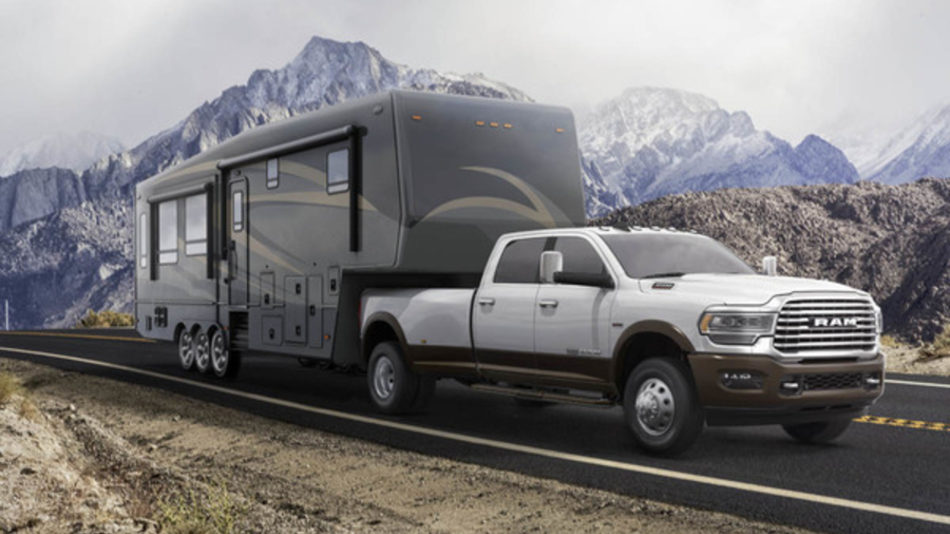 A white RAM 3500 hauls a cattle trailer down a country road, mountains in the background