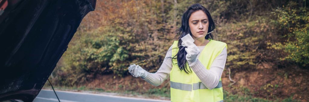 A young woman in a white shirt and yellow vest checks her oil dipstick next to the open hood of her car on the side of the road