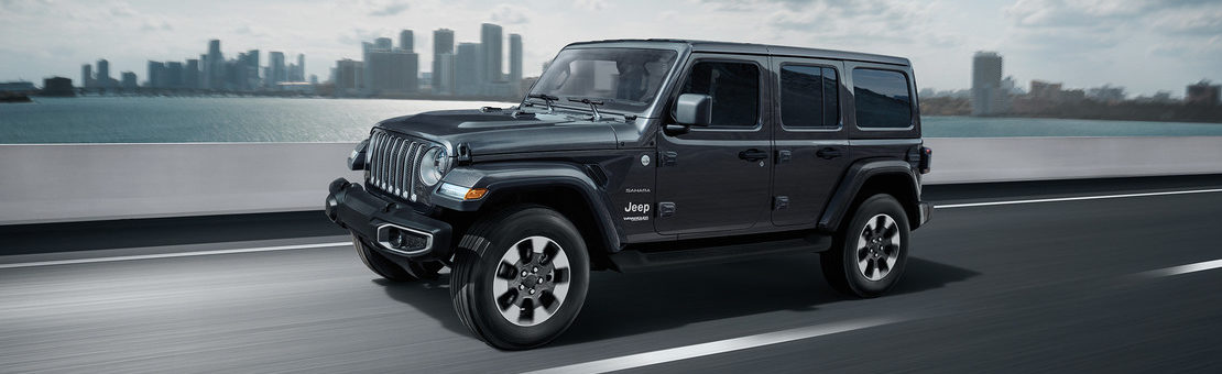 2019 Jeep Wrangler JL Sahara driving on a road with a city in the background