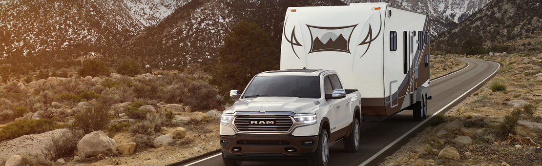 2019 Ram 1500 hauling a camper driving by mountains in the country