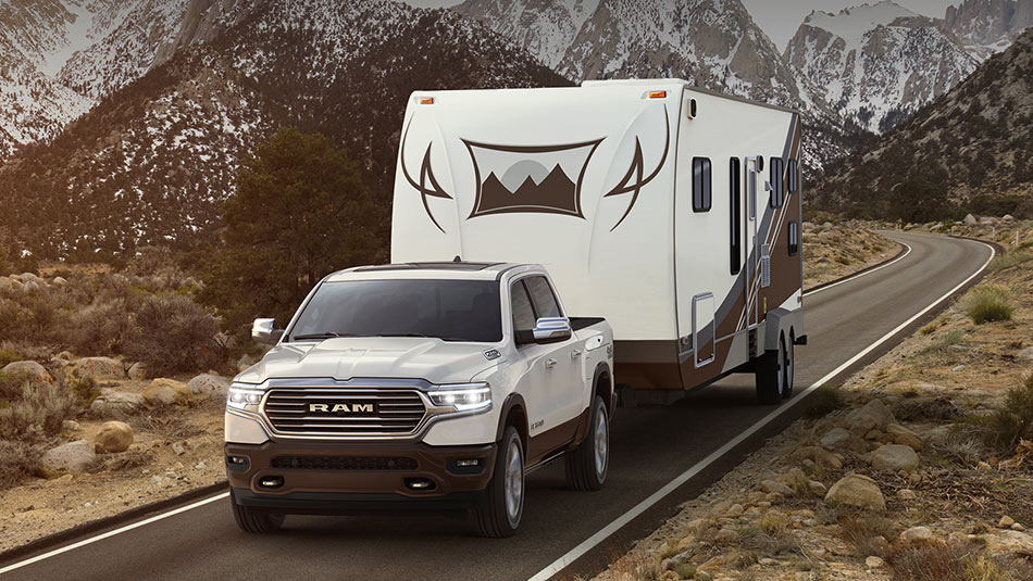 2019 RAM 1500 towing a trailer down the highway