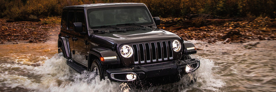 2019 Jeep Wrangler JL Trail Rated driving through a river