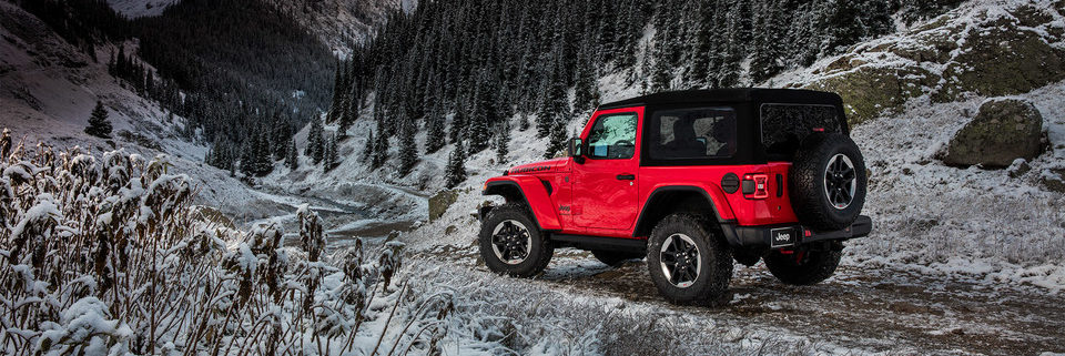2019 Jeep Wrangler JL on a snowy road in front of a mountain