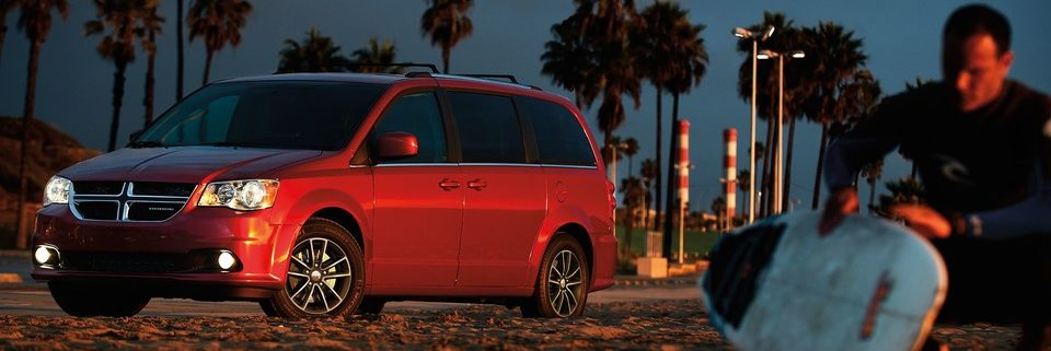 2019 Dodge Grand Caravan on the beach at night with a surfer